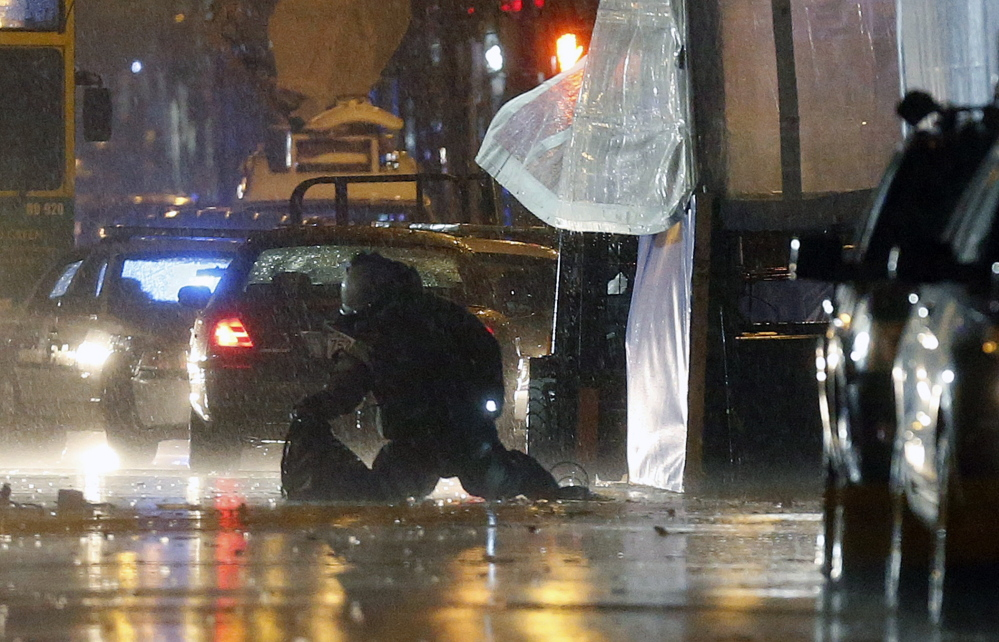 """A member of the bomb squad inspects an object found at the finish line of the Boston Marathon Tuesday. Police later blew up the two unattended backpacks and took Kevin """"Kayvon"""" Edson, 25, into custody in connection with one of them."""