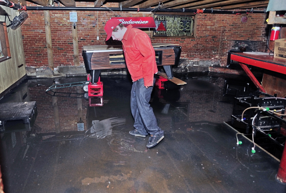 About an inch of water remains in the deepest spots where Brian Nichols inspects the back room of the Kennebec Wharf on Thursday in Hallowell.