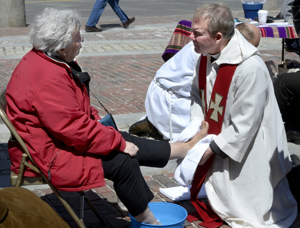 Sister Dale Jarvis of Portland, with the Sisters of Mercy, gets her feet washed by the Rev. Tim Higgins from St. Ann's Episcopal Church in Windham during a Holy Thursday foot washing by clergy from area churches at Monument Square in Portland.