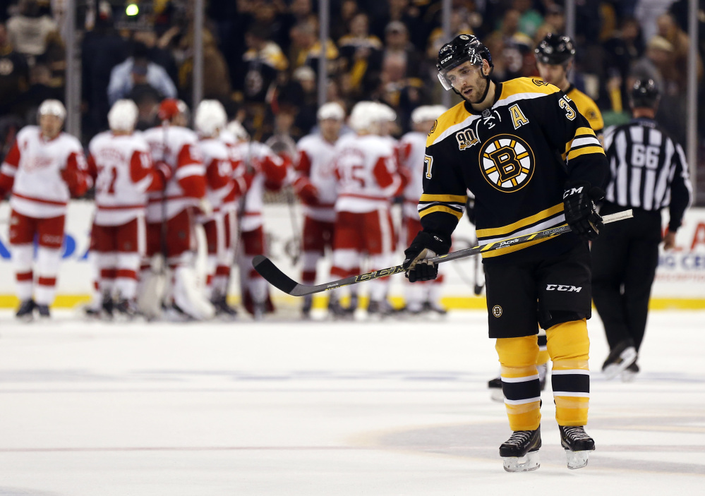 Boston Bruins' Patrice Bergeron skates off the ice as the Detroit Red Wings celebrate their 1-0 win in Game 1 of a first-round NHL playoff hockey series, in Boston on Friday, April 18, 2014.