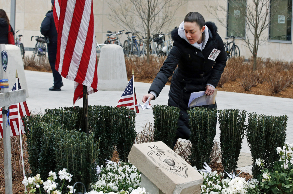 Massachusetts Institute of Technology employee Jennifer Earls places a folded paper crane near a memorial Friday for MIT Officer Sean Collier in Cambridge, Mass.