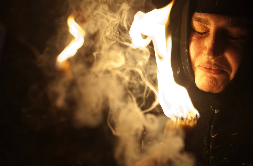 A Christian pilgrim during the ceremony of the Holy Fire in Jerusalem. The flame was passed among worshippers outside the Church of the Holy Sepulcher and then taken to the Church of the Nativity in the West Bank town of Bethlehem, where tradition holds Jesus was born, and from there to other Christian communities in Israel and the West Bank.