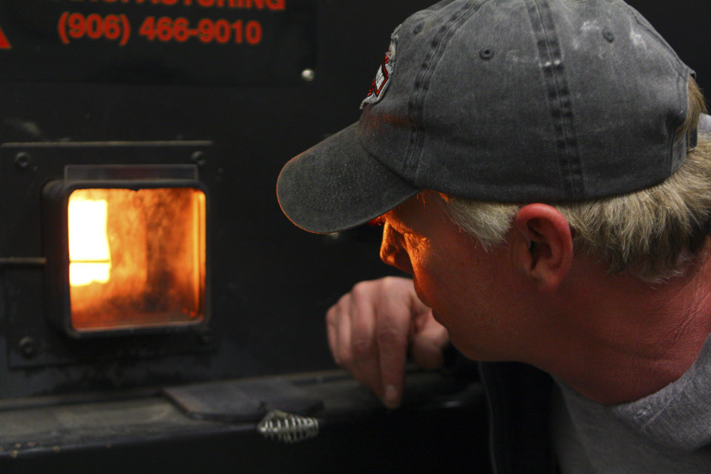Jeff Woodbury, assistant school facilities director checks, on a wood heat furnace used by schools in Falmouth. The furnace was partially funded by a grant of federal stimulus dollars to the Maine Forest Service. The grant program helped 24 facilities slash costs for the heating season ending in 2013 by replacing upward of 900,000 gallons of heating oil with locally produced wood chips and pellets.