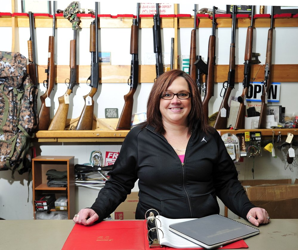 Ashley Preble, manager of Webster's Trading Co. in Auburn, stands behind the gun counter with registrations of buyers she says are confidential to the public but open to any federal agent who wants to see the records.