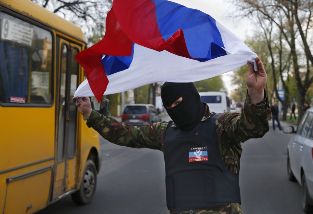 """A masked pro-Russia demonstrator waves the Russian flag in Donetsk, eastern Ukraine, on Tuesday. U.S. Vice President Joe Biden warned Russia on Tuesday that """"it's time to stop talking and start acting"""" to reduce tension in Ukraine."""