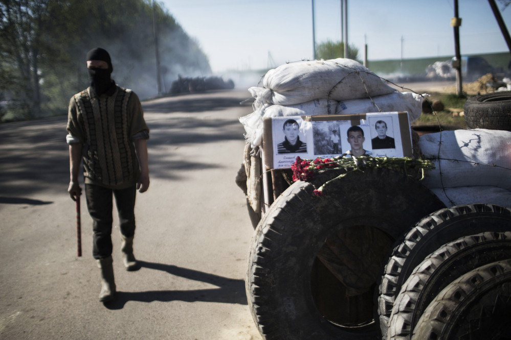 A masked pro-Russia man walks next to a barricade with pictures of three pro-Russia militiamen killed days ago at a checkpoint by Ukrainian forces near Slovyansk, Ukraine, on Thursday.