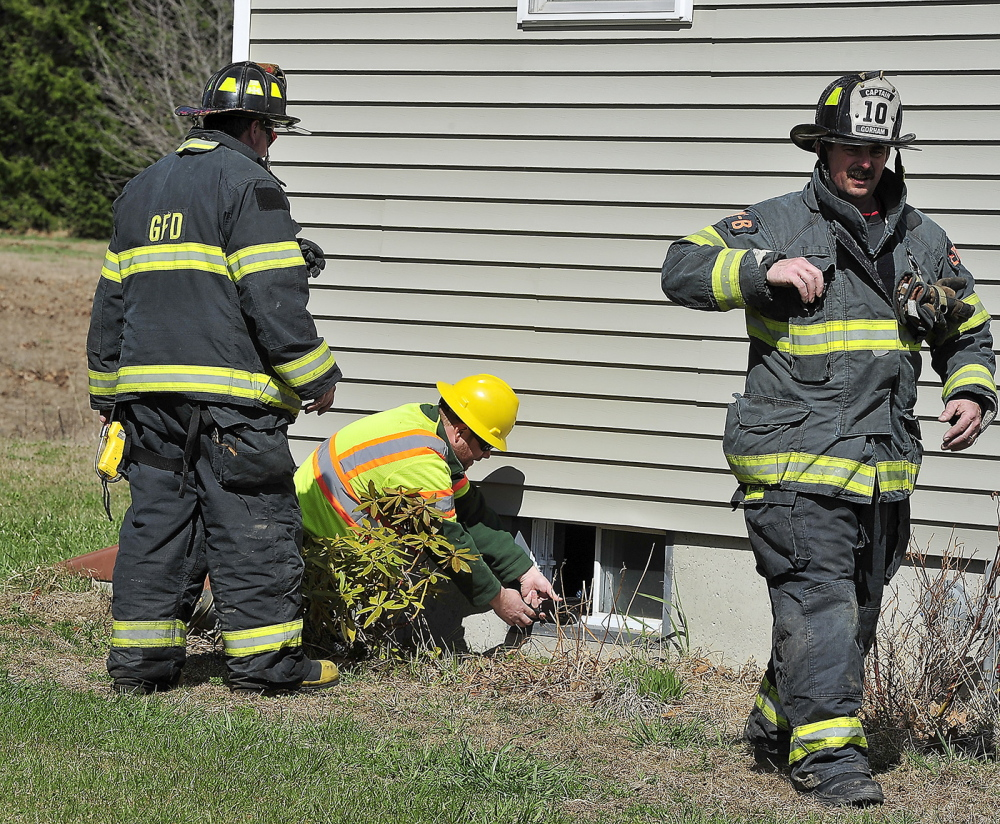 With help from Gorham firefighters Jason Baker, left, and Terry Deering, Maine Natural Gas technician Ron Dube checks for gas levels in this unoccupied home after a gas main was ruptured at Hawkes Farm development in Gorham.