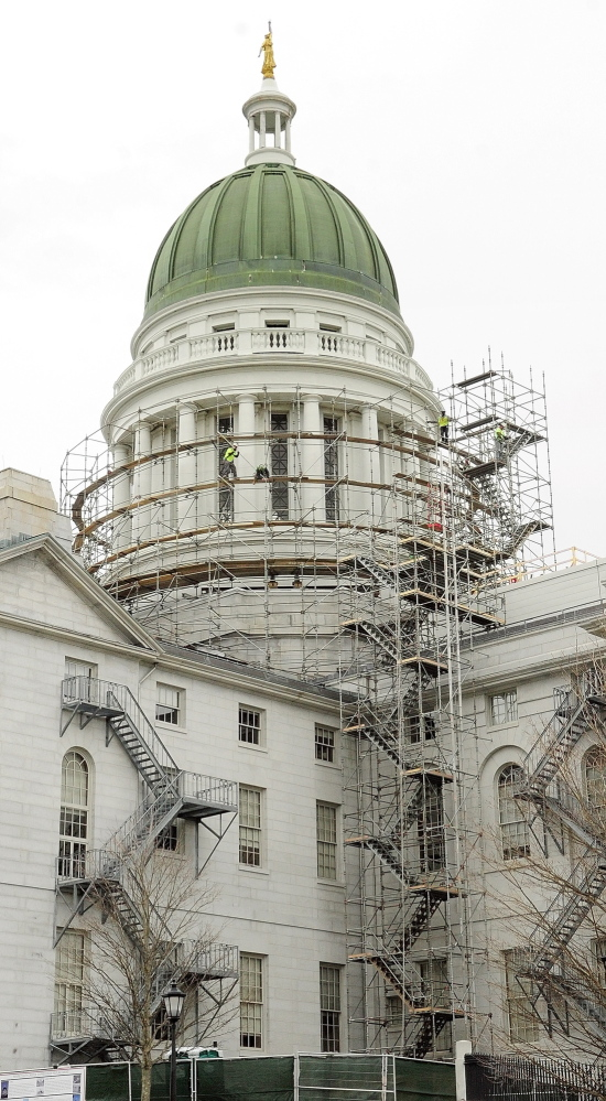 Workers build scaffolding around the State House dome on Wednesday in Augusta. A $1.3 million project entails restoring the dome's copper sheathing and gilding the statue that tops it.
