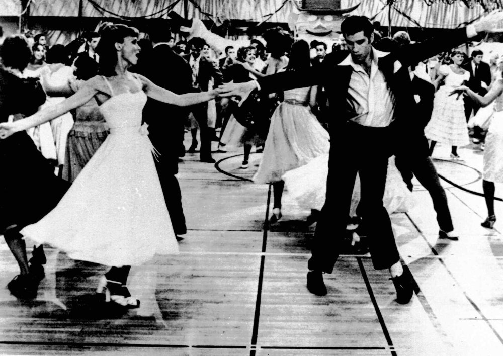 """This undated image originally released by Paramount Pictures shows John Travolta, right, and Olivia Newton-John in a scene from the film """"Grease."""" Fox jumped into the theater game Monday."""