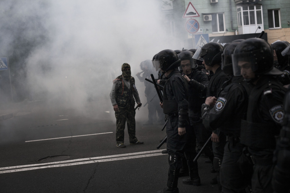 A pro-Russian activist shouts to police after the explosion of a gas device during a pro-Ukraine rally in Donetsk, Ukraine, on Monday.