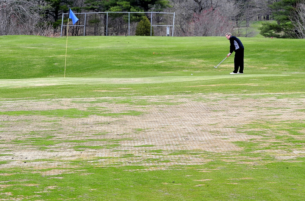"""Andy McInnis of Portland, a member of Riverside Golf Course for the past 20 years, putts Monday on the temporary green at the 6th hole. It is one of many greens that have been adversely affected by winter ice at Riverside and other local courses. """"This is the worst I've seen it,"""" McInnis said."""
