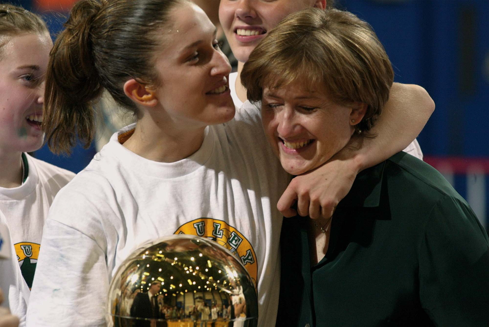 """Sarah Marshall and Coach Elizabeth Rickett join in the celebration after winning the state Class A girls' basketball championship in 2003. Marshall Ryan says her years at McAuley """"some of the best years of my life."""""""