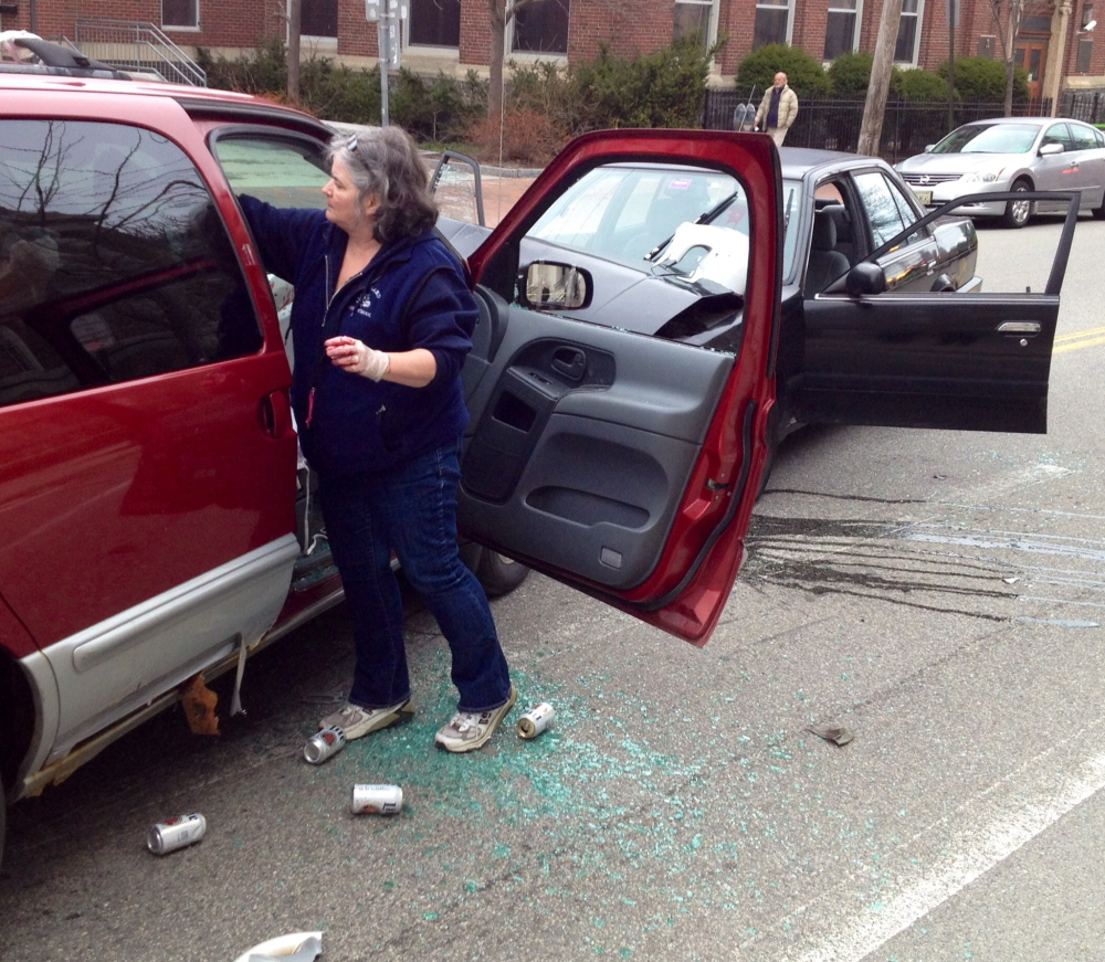 Liz Bryant, guidance secretary for Portland High School, pours simulated blood on the cars as she helps set up a staged accident scene in front of the school on Cumberland Avenue in Portland.