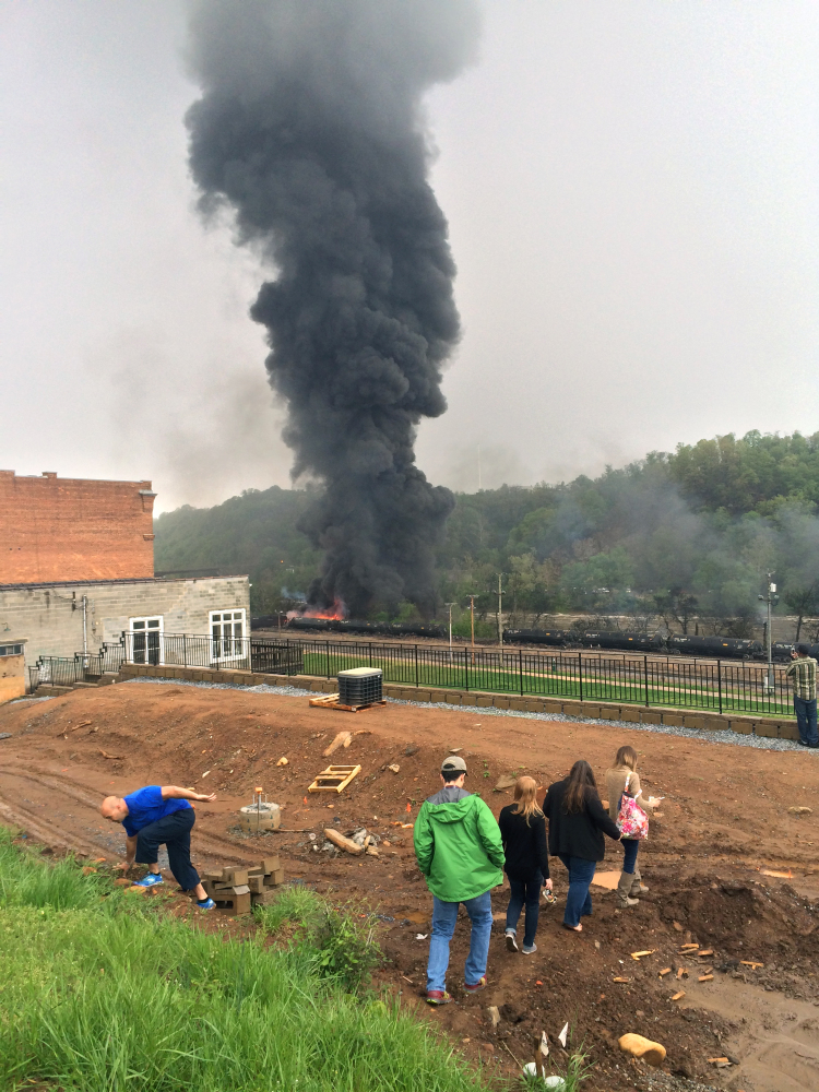 Smoke rises after several CSX tanker cars carrying crude oil derailed and caught fire Wednesday in Lynchburg, Va. Authorities evacuated numerous buildings after the derailment.