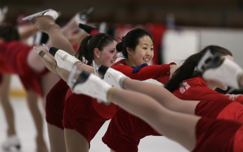 In this Wednesday, March 19, 2014 photo, Devin Wang, a Boston University student and skater with the USA synchronized skating team known as the Haydenettes, practices in Lexington, Mass. Wang, along with bystander Carlos Arredondo and EMT Paul Mitchell, are credited with helping to save the life of Jeff Bauman, who suffered traumatic injuries in the Boston Marathon bombings.