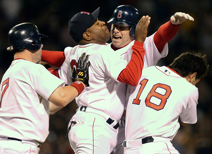 Boston Red Sox players, from left, Trot Nixon, first base coach Dallas Williams, Shea Hillenbrand and Johnny Damon celebrate after Hillenbrand drove in the winning run in the ninth inning against the Tampa Bay Devil Rays in this April 15, 2003, photo. The Red Sox won 6-5 in Boston.