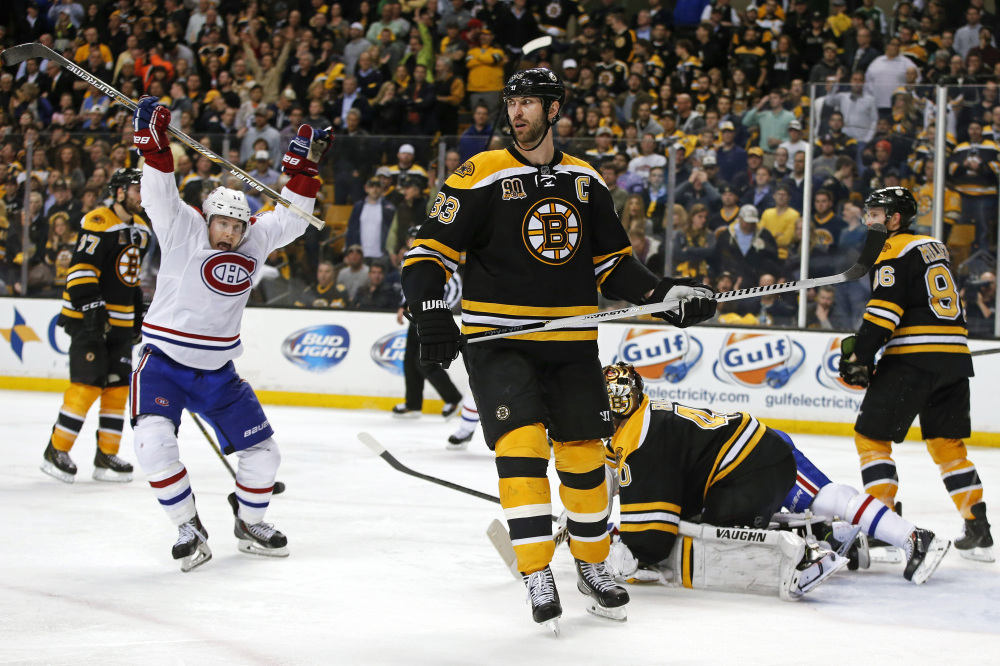 Montreal Canadiens right wing Brendan Gallagher celebrates his teammate P.K. Subban's game-winning goal in the second overtime period as Boston Bruins defenseman Zdeno Chara (33) skates past in Game 1 of the second-round Stanley Cup playoff series in Boston on Thursday.