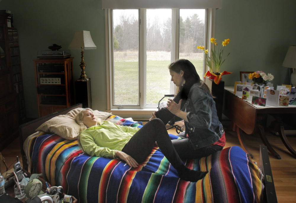 Eileen Whynot, 58, stretches with the help of her physical therapist, Sarah Dudley, at Whynot's home in Gorham on Tuesday. Whynot broke her pelvis and left hip in a serious ski accident at Sunday River last month and is grateful for having purchased health insurance through the Affordable Care Act.