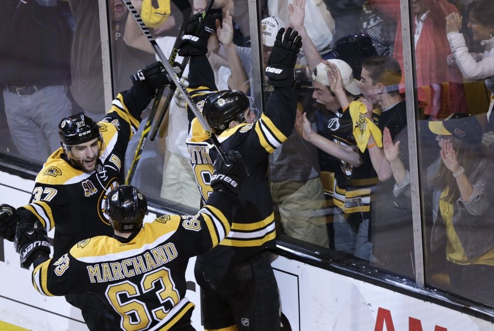 Reilly Smith, 18, of the Bruins celebrates his goal against the Canadiens during the third period of Game 2 in the second round of the playoffs in Boston Saturday. The Bruins won 5-3, tying the best-of-seven games series at one game each. At left are Patrice Bergeron, 37, and Brad Marchand.