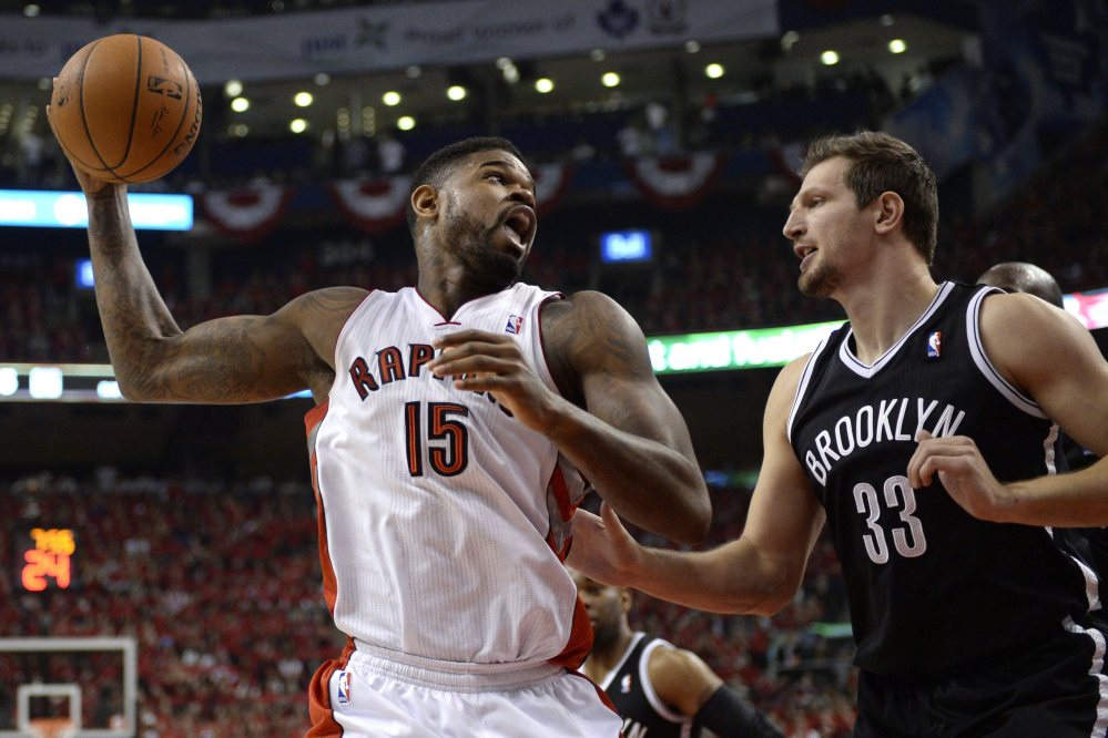 Toronto's Amir Johnson, left, works against Brooklyn's Mirza Teletovic in the first half of Game 7 at Toronto on Sunday. The Nets advanced with a 104-103 win.