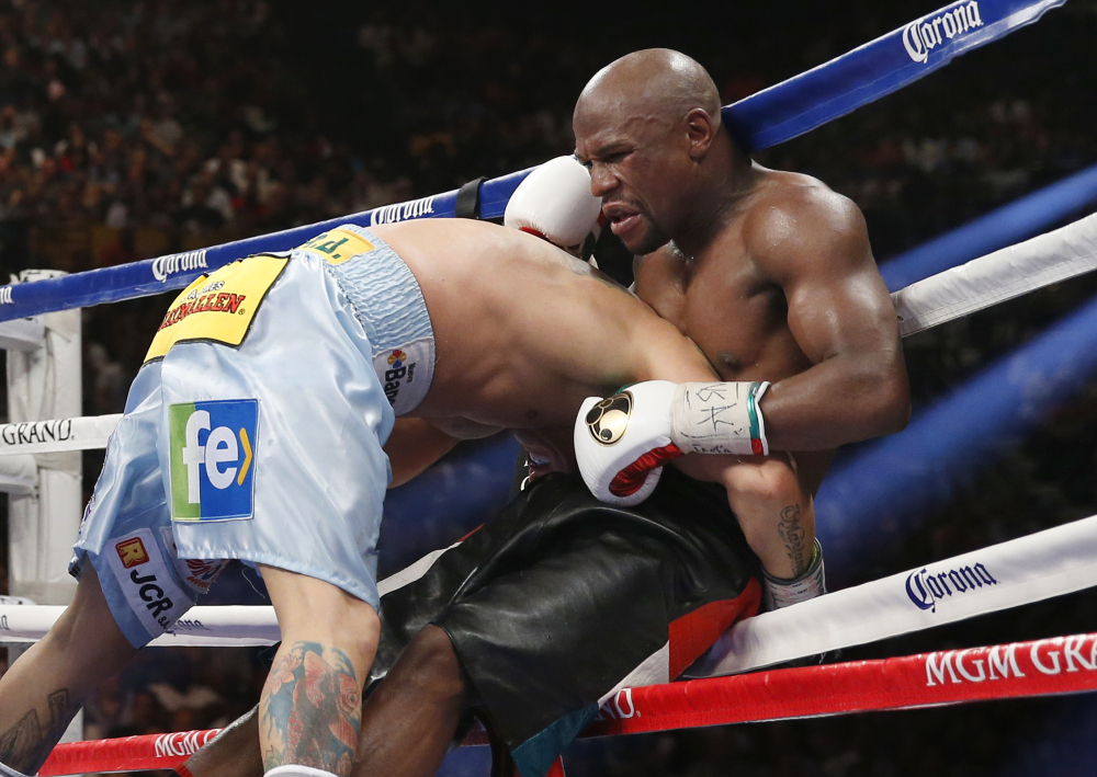 Floyd Mayweather Jr. is driven through the ropes by Marcos Maidana in their WBC-WBA welterweight title boxing fight on Saturday, in Las Vegas. Mayweather won by majority decision.