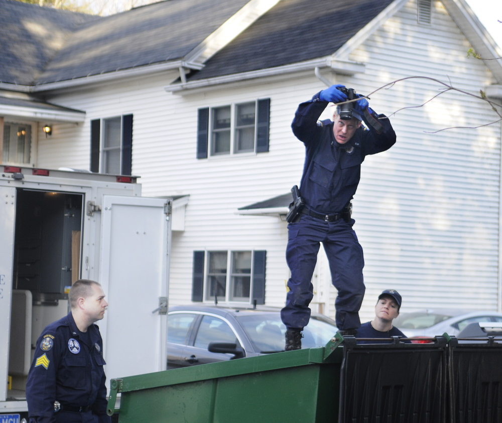 Maine State Police Detective Terry James, center, photographs the interior of a Dumpster on Monday outside of the apartment that Leroy Smith Jr. shared with his son, Leroy Smith III, in South Gardiner. Detective Sgt. Jason Richards, left, and Trooper Breanne Petrini searched the Dumpster after the elder Smith's body was recovered in Richmond.
