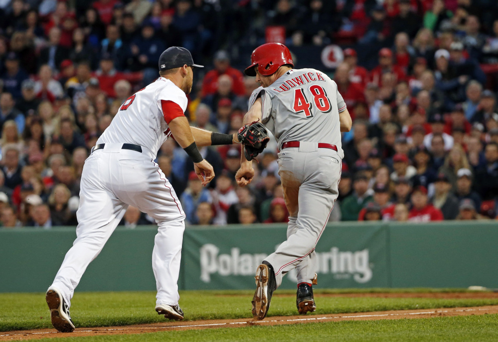 Cincinnati Reds' Ryan Ludwick (48) is tagged out by Boston Red Sox third baseman Will Middlebrooks during a rundown between third and home in the second inning of a baseball game at Fenway Park in Boston, Tuesday, May 6, 2014.
