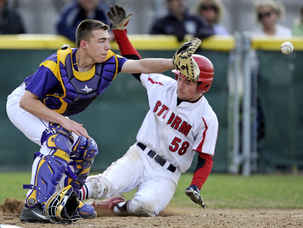 Cheverus catcher Logan McCarthy takes a late throw as Zach Carreiro of Scarborough slides safely home, scoring on a Ben Greenberg single in the third inning Tuesday during a 2-0 victory. The win is the Red Storm's first of the year.