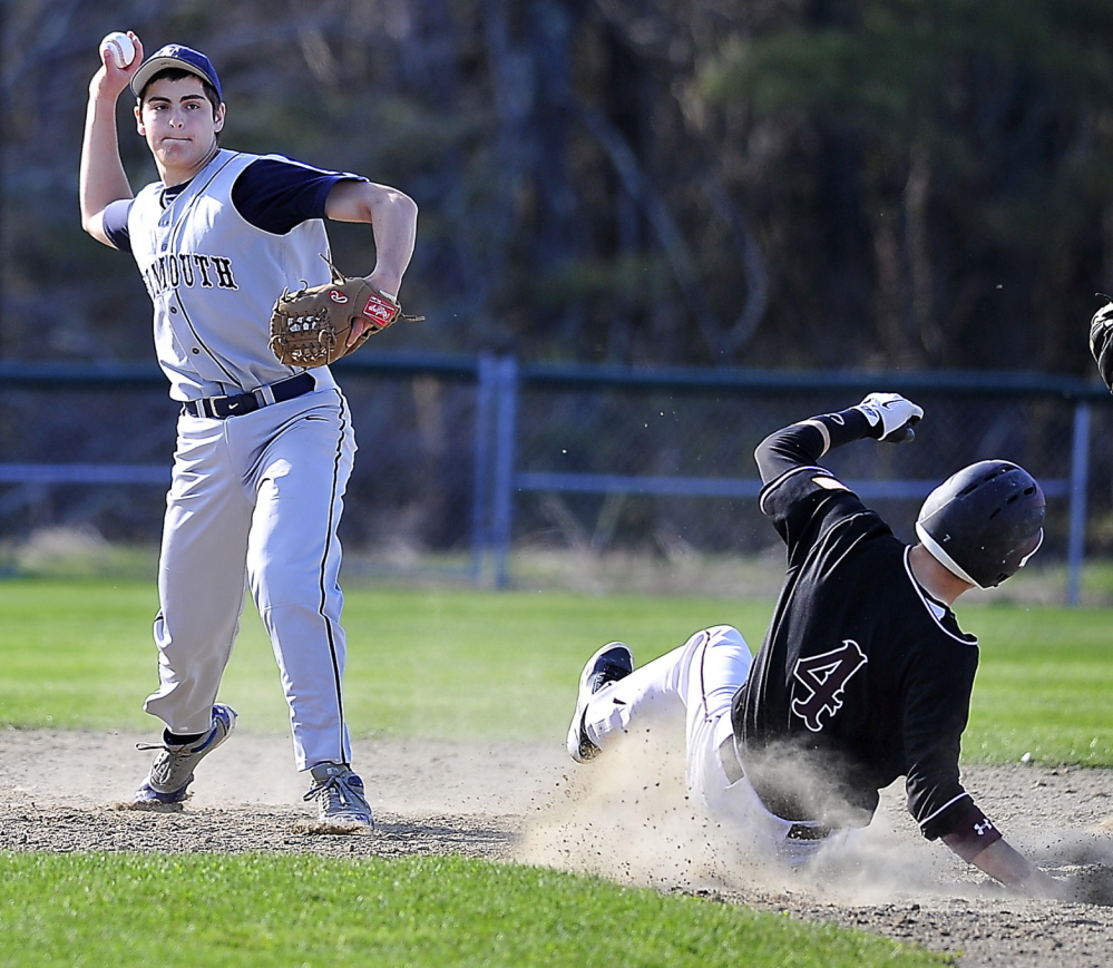 Shortstop Cody Cook of Yarmouth throws to first base to end an inning as Miles Shields of Greely slides into second base during their Western Maine Conference game at Cumberland.