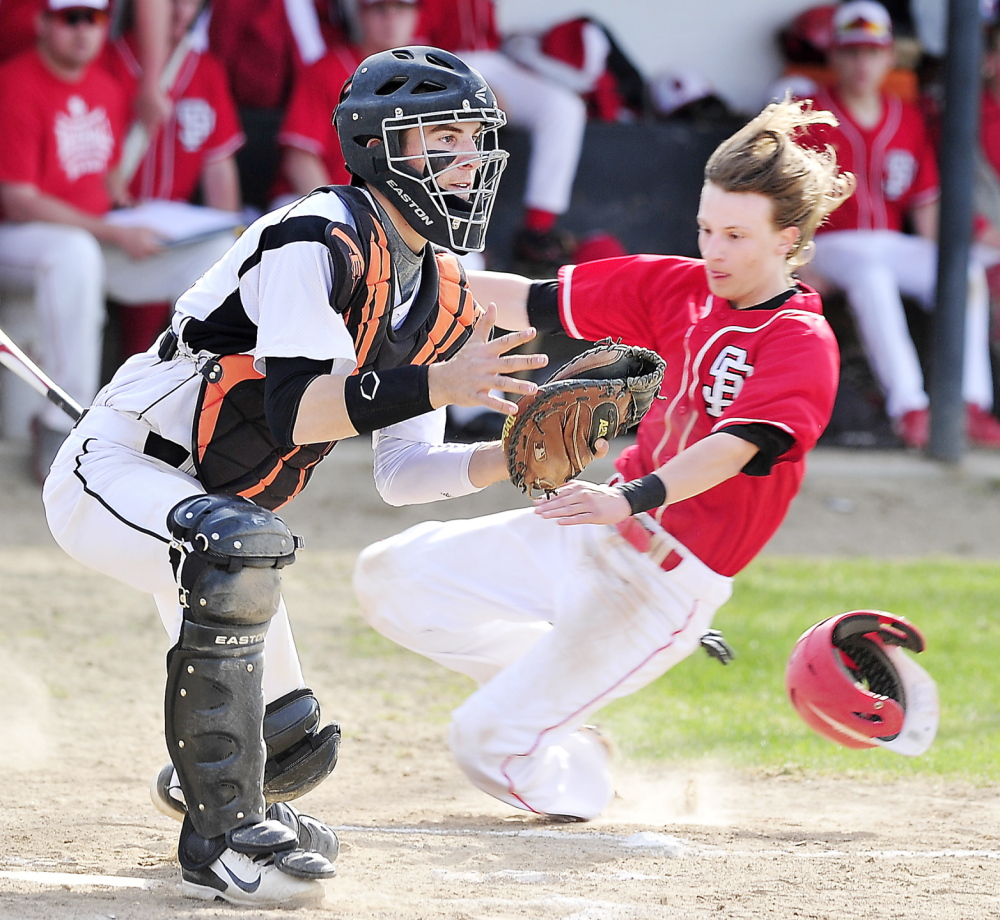 Cosmo Romano of South Portland slides across the plate as Biddeford catcher Corey Brown waits for a throw from center field during their SMAA game at Biddeford.