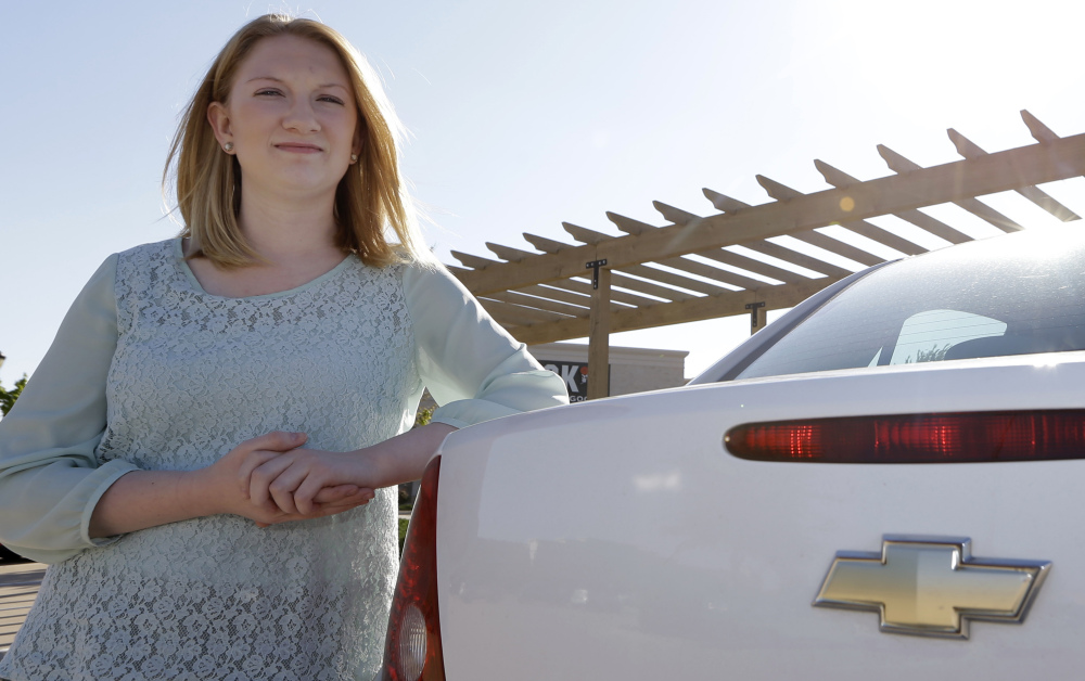 Wendi Kunkel leans her 2010 Chevy Cobalt in Rockwall, Texas, on April 18. She was instructed by her dealer to pull everything off her key ring to stop the ignition switch from turning off unexpectedly, but she's still nervous about driving her car.
