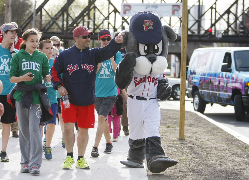 """Justin LeBlanc, who was inseparable from Slugger, the Sea Dogs' mascot, for three years although they never were seen together, walks with an entourage Thursday on the final steps to Hadlock Field, completing a five-day trek (""""Was that a seal I just saw walking down the road?"""") from Fenway Park."""