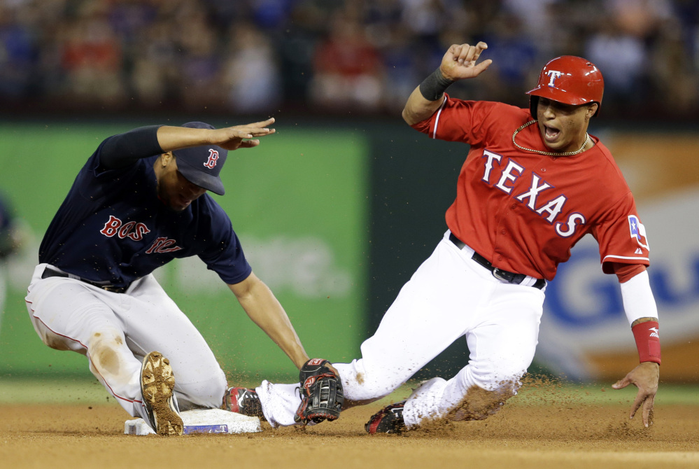 Red Sox shortstop Xander Bogaerts, left, is knocked backward after tagging out Leonys Martin of the Rangers as Martin was trying to steal second in the fourth inning.