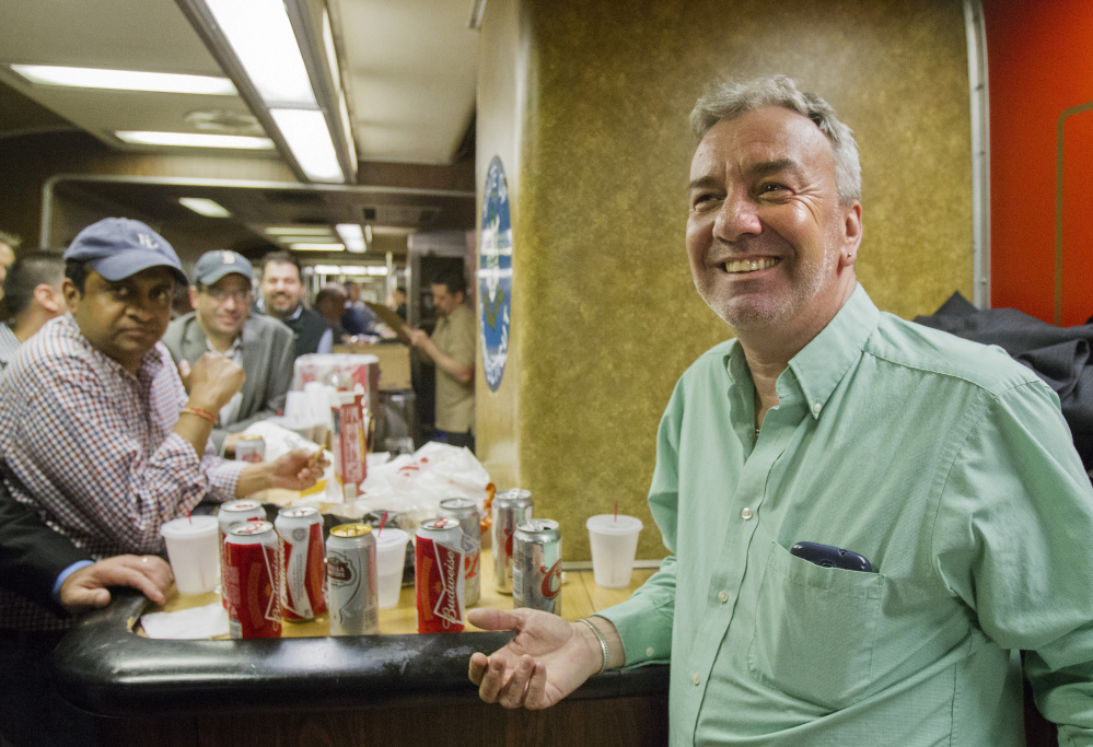 """Mark DeMonte, right, of Wallingford, Conn., joins other riders in the bar car on the train to New Haven, Conn. DeMonte, a bar car regular, has been dubbed """"Mayor of the 5:48"""" by friends and riders."""
