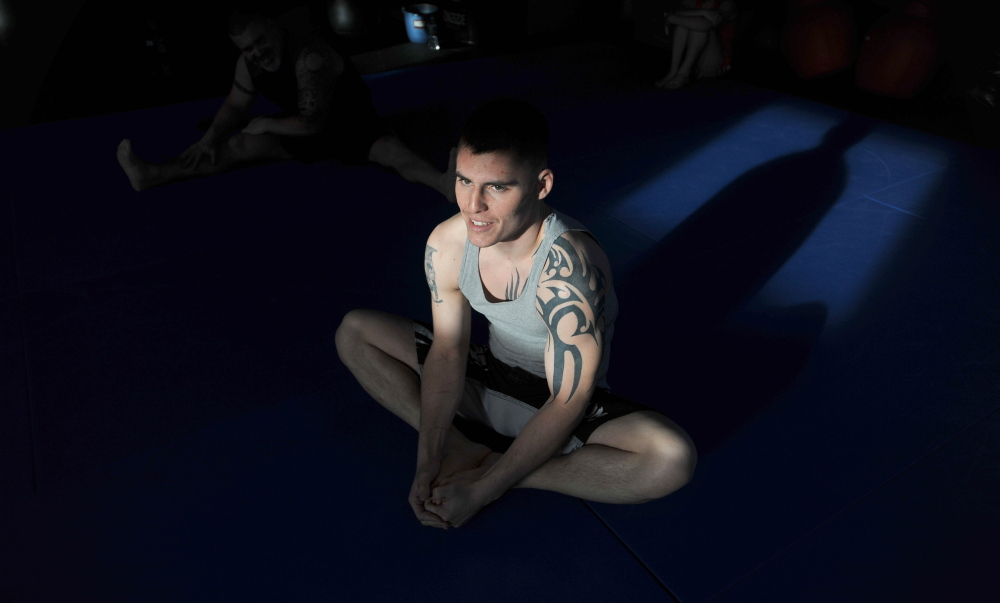 Mixed martial arts participant Phillip Exner stretches before a training session at Littlefield's Gym in Oakland on Thursday.