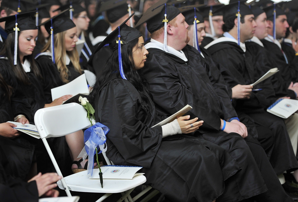 A single white rose tied with a blue ribbon rests on an empty chair during the Saint Joseph's College graduation in Standish. The rose honors the memory of Clark Noonan, a basketball player who died in a car crash in April 2012.