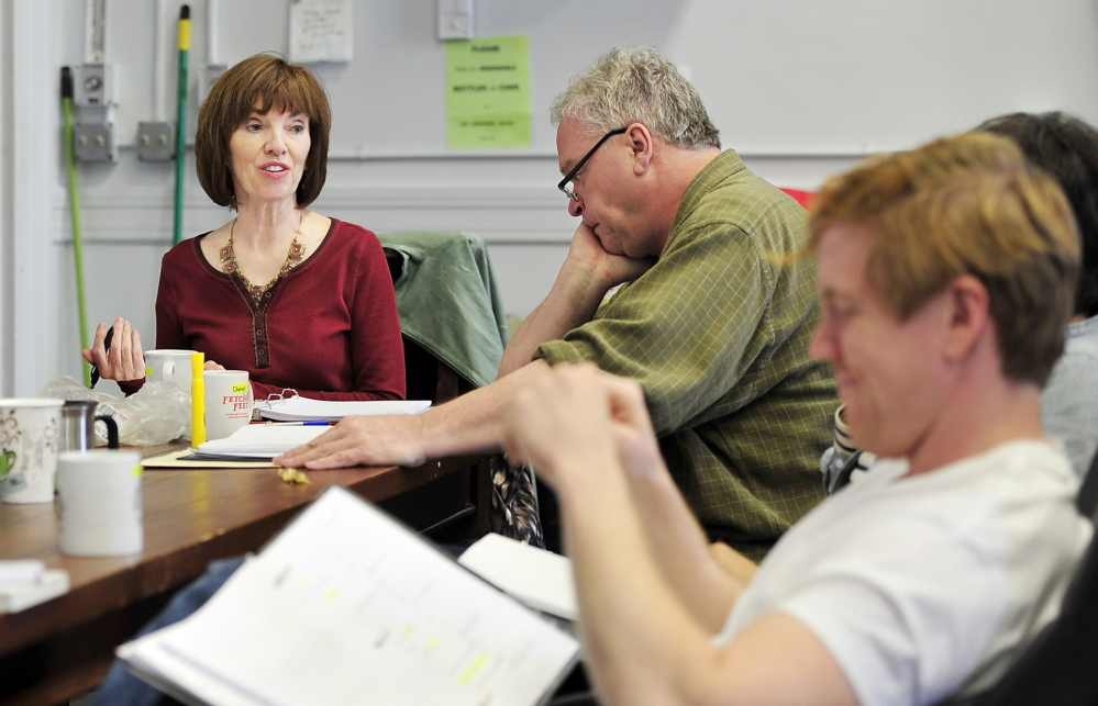 """Monica Wood meets with Portland Stage Company actors – including Daniel Noel, center, and Dustin Tucker, foreground – during a reading of her play """"Papermaker."""" The work is based on an earlier novel, """"Ernie's Ark,"""" which centers on two families who collide during a strike at a paper mill."""