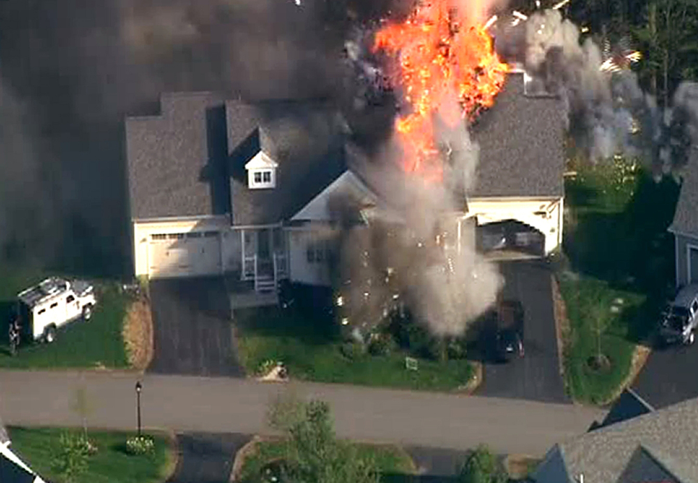 In these frame grabs from television helicopter video, a police SWAT team, left, is parked on the lawn of a home in Brentwood, N.H., as it explodes into flames, Monday, May 12, 2014. Shots were fired just before the fire, which involved a police officer, according to the New Hampshire State Police.