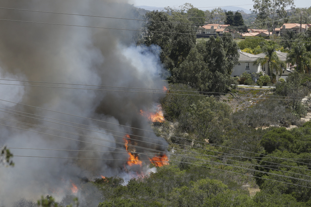 Wildfire climbs a canyon toward homes Wednesday in Carlsbad, Calif.