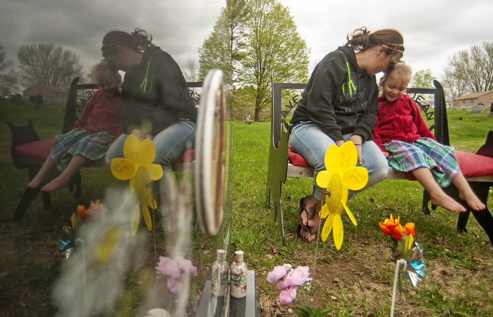 Riley Souzer, 2, cuddles with her mother, Tabitha Souzer, at the grave site of her half sister Avery Jean Lane at North Fairfield Friends Meeting House cemetery Thursday.