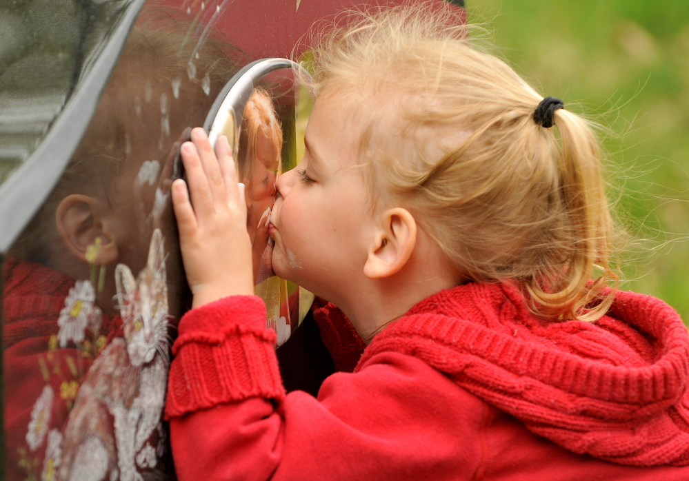 Riley Souzer, 2, kisses the headstone of her half sister Avery Jean Lane at North Fairfield Friends Meeting House cemetery on Thursday. It's something Riley does each time she visits Avery's resting place. Avery's grave site was recently vandalized and authorities are still searching for the culprits.