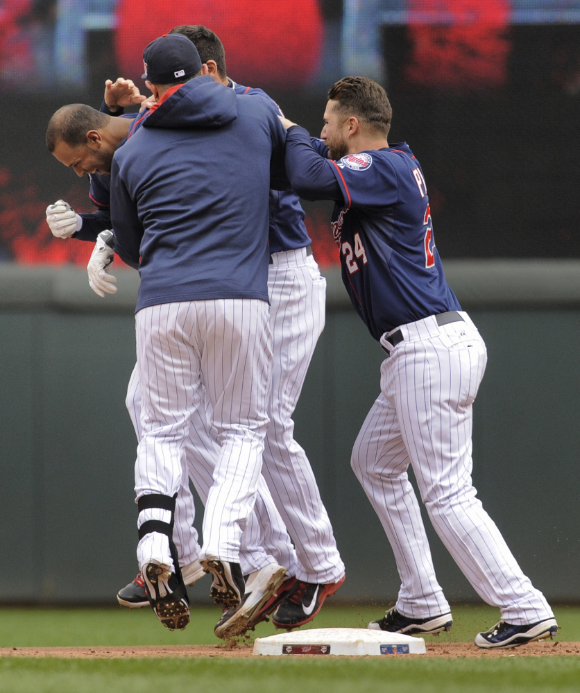 Teammates mob Minnesota Twins center fielder Aaron Hicks after he singled to bring in the winning run against the Boston Red Sox in the 10th inning in Minneapolis on Thursday.