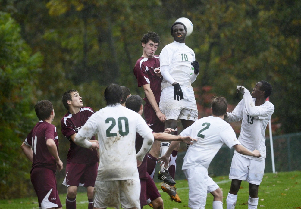 Greely's Sam Porter and Waynflete's Paul Runyambo go up over the the crowd trying to gain possession of the ball during soccer action in October 2012.
