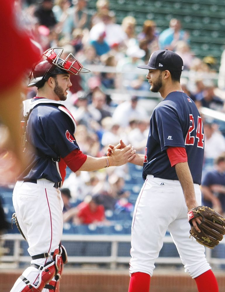Sea Dogs catcher Blake Swihart gives a hand to relief pitcher Noe Ramirez, who had a 1-2-3 ninth inning after starter Mike Aguliera went eight strong innings in a win at Hadlock Field on Sunday.