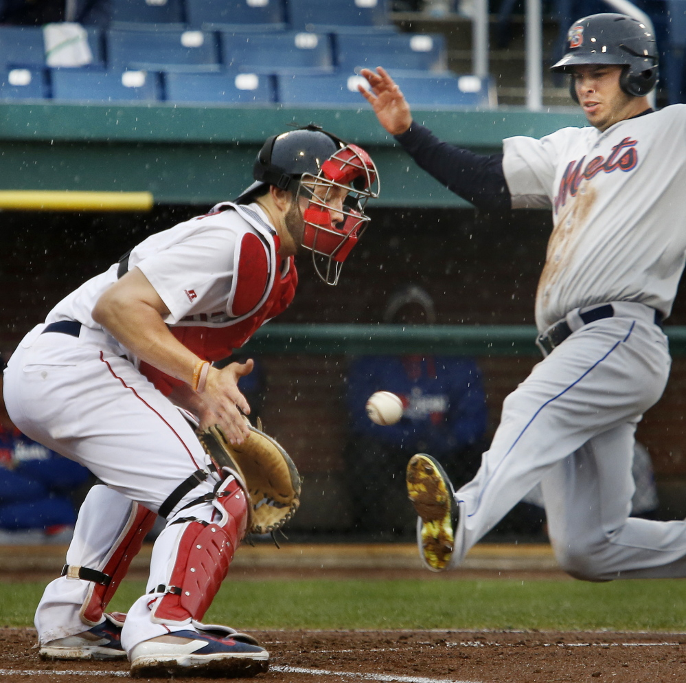 Matt Clark of the Binghamton Mets scores in the fourth inning of the first game Monday night as catcher Blake Swihart of the Portland Sea Dogs waits for the throw. Binghamton won the first game 5-0, but the Sea Dogs came back for an 8-2 victory in the second game at Hadlock Field.