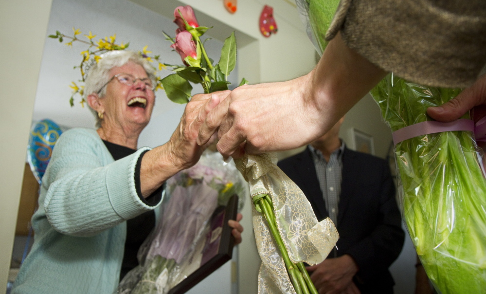 Agnes Dugas receives flowers while being honored for 18 years of volunteering at the Sagamore Health Center in Portland on Tuesday.