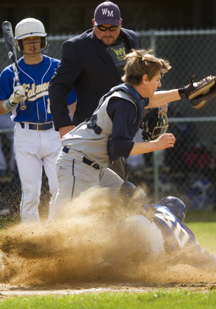 Connor Aube of Falmouth slides safely into the plate as Yarmouth catcher Ryan Nason collects a late throw during the first inning of their game at Falmouth.