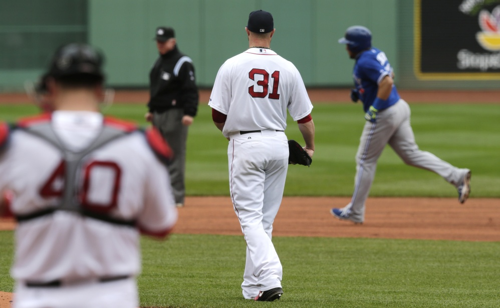 Boston Red Sox starting pitcher Jon Lester (31) watches Toronto Blue Jays' Melky Cabrera, right, round the bases on a solo home run during the first inning of a baseball game at Fenway Park, Thursday, May 22, 2014, in Boston.