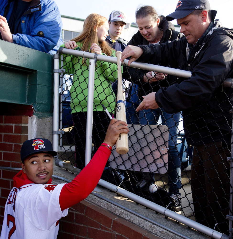 Mookie Betts, handing an autographed bat back to Jon Barton of Sanbornville, New Hampshire, has been a sensation with the Sea Dogs and may get a promotion to Triple-A sooner rather than later.