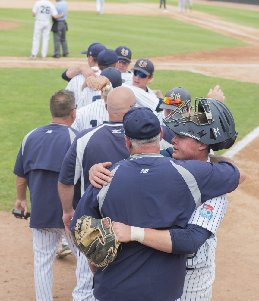 University of Southern Maine's catcher Matt Verrier gets a hug after being removed from the game with other seniors in the ninth inning Monday in Appleton, Wis.